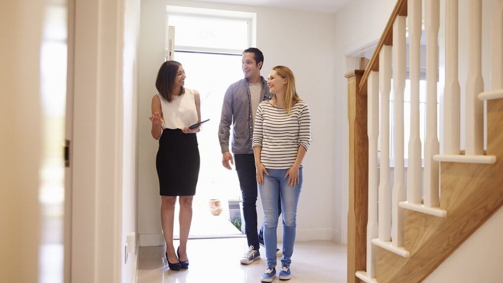 real estate agent showing couple around home