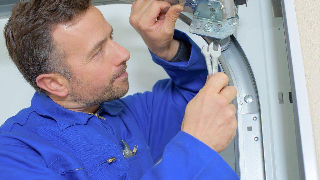 man fixing wheel/mechanism attached to garage door rail