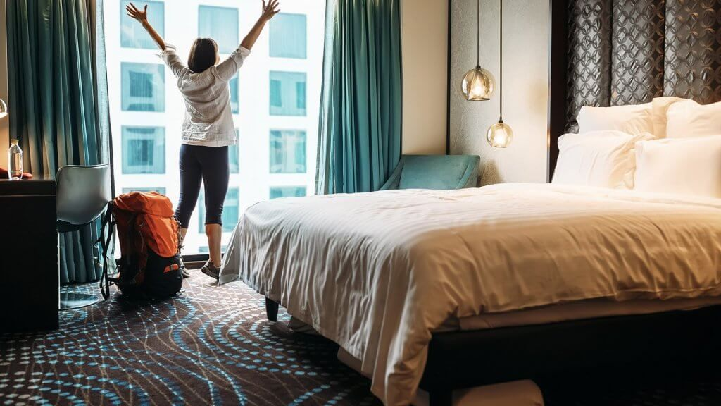 excited woman in hotel room
