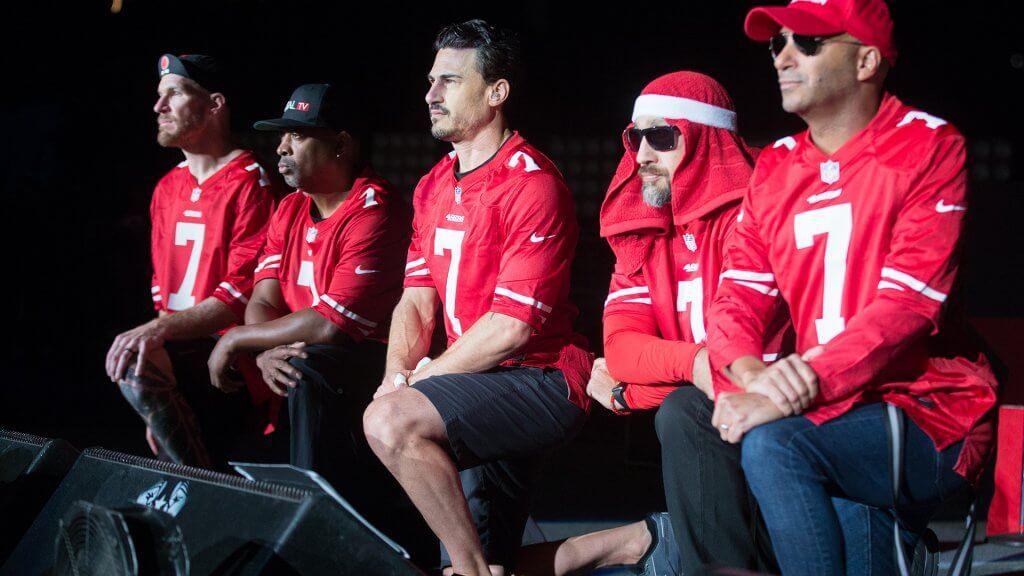 men in Colin Kaepernick jerseys kneeling