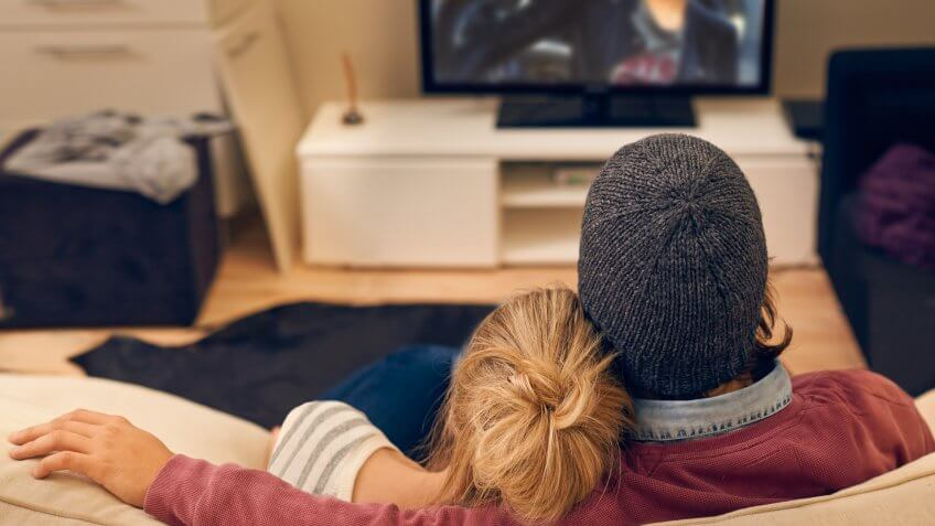 Rear view shot of a young couple watching TV together.