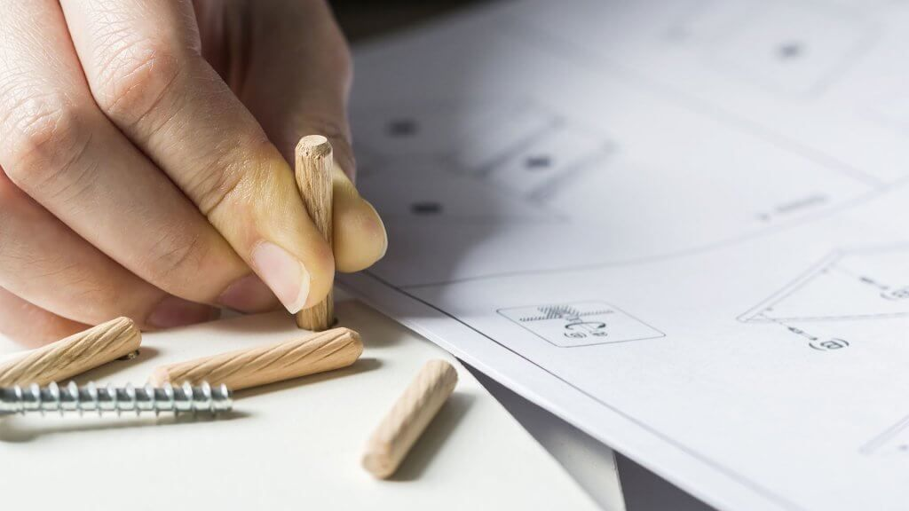 person holding tiny wooden part for ikea product
