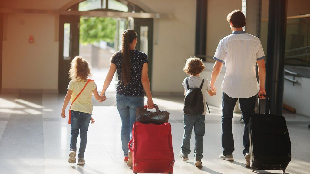 family of four with bags and other luggage