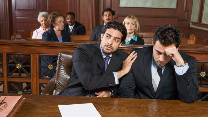 Two men sitting in court.