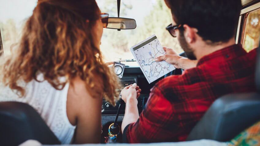 Rear view of a young couple in their car checking a map