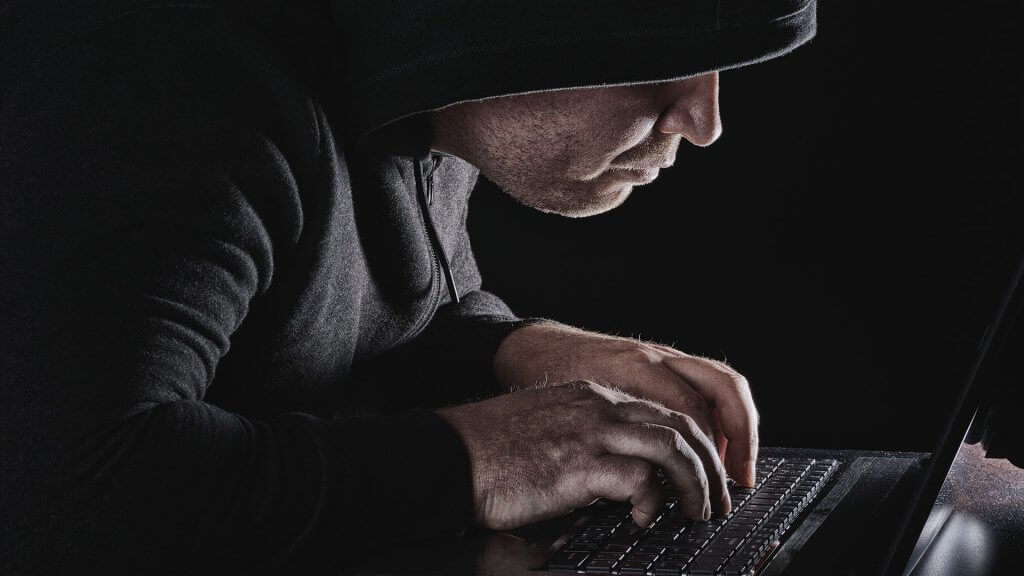 shady-looking man in black typing on laptop in dark room