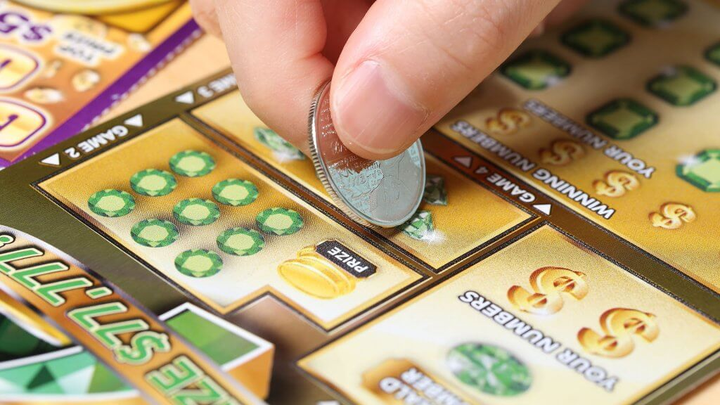 person playing scratch-off lottery ticket