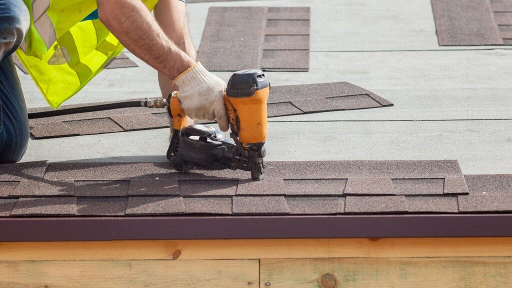 roofer applying shingles with power tool