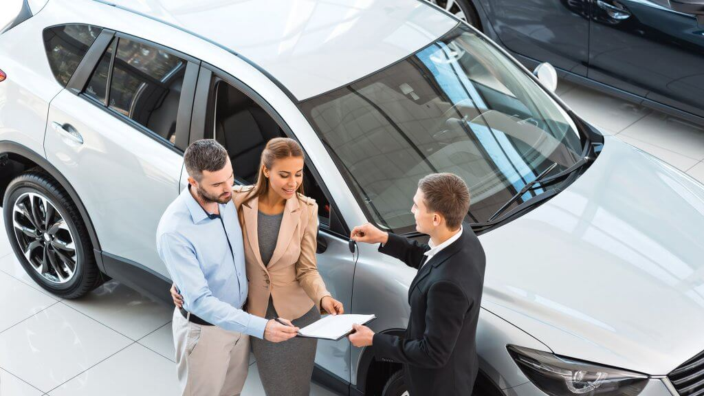 overhead shot of couple buying a new car