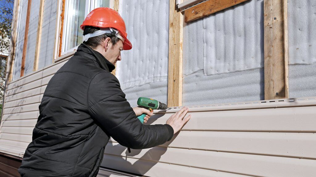 man using power drill on house that's under construction