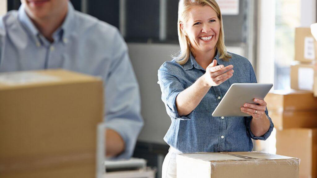 woman with tablet in room full of moving boxes