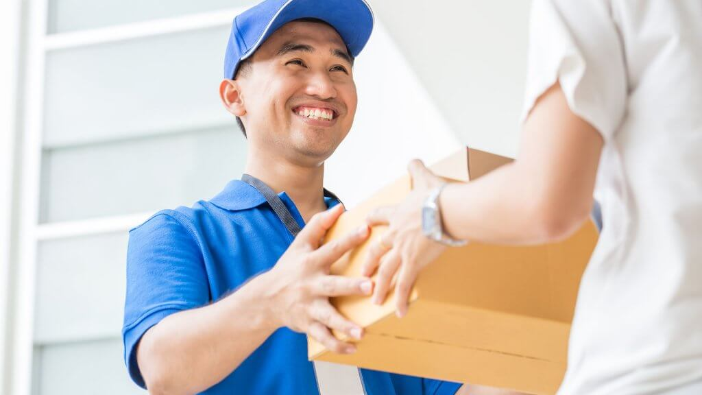 deliever man handing woman package