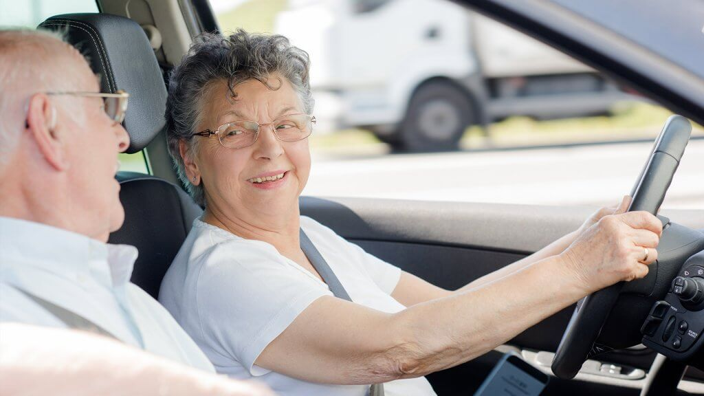 elderly woman driving with husband