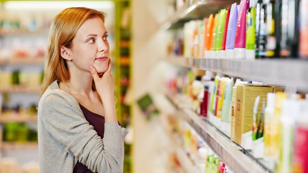 woman deciding on which product to buy in store