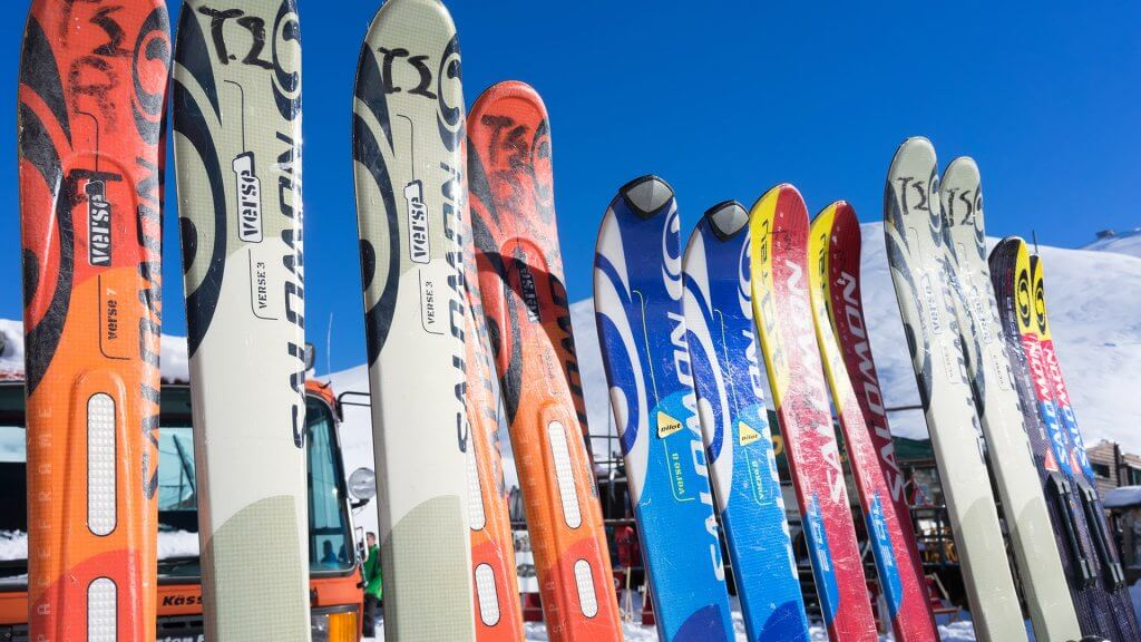 several pairs of rental skis resting on a rack