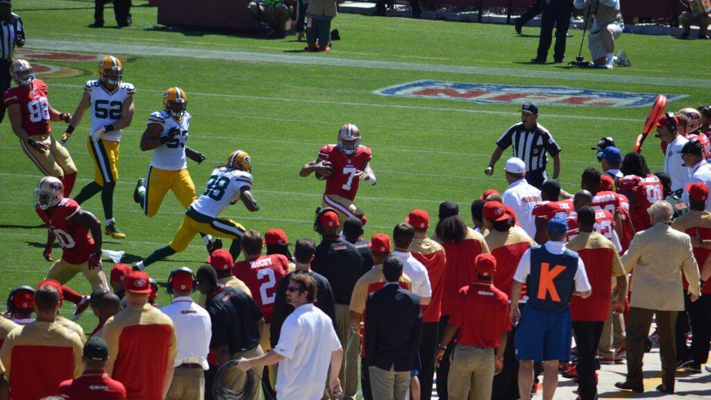Colin Kaepernick running with football
