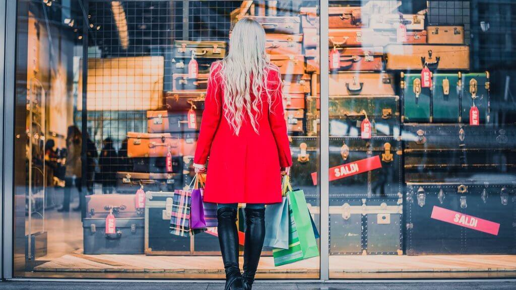 woman with shopping bags and standing in front of store window