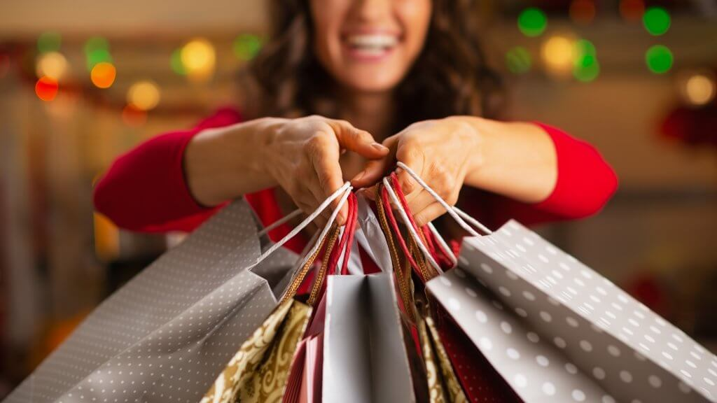 woman holding out gift bags