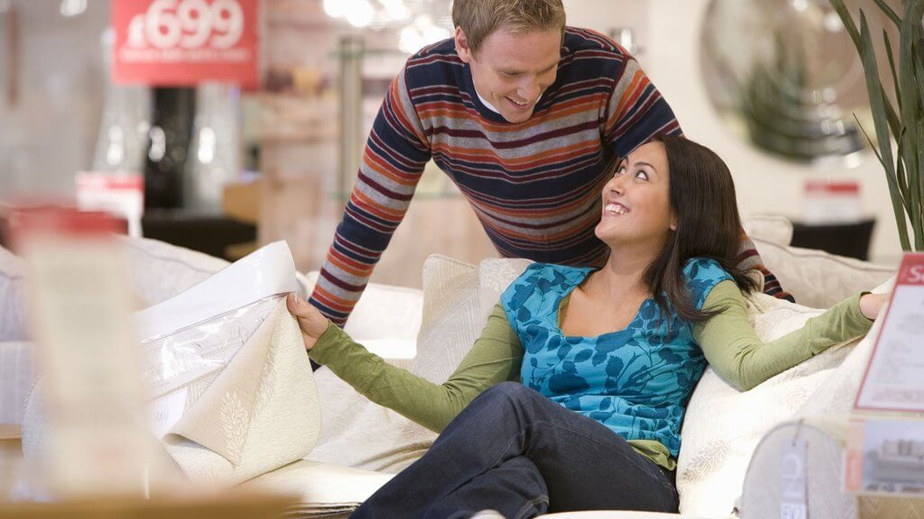 couple checking out ikea couch in store