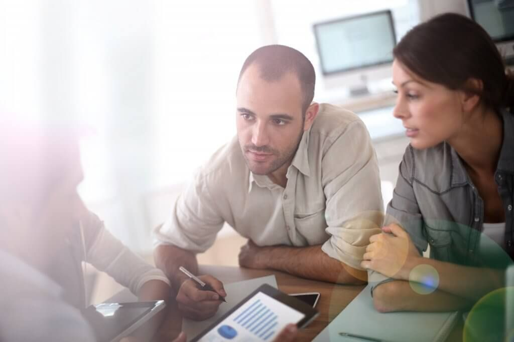man and woman talking to financial planner