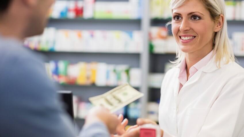 Customer paying with cash in pharmacy.