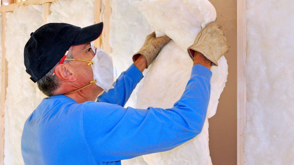 man with facemask on installing insulation
