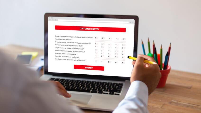 Businessman Filling Survey Form Online on Computer.