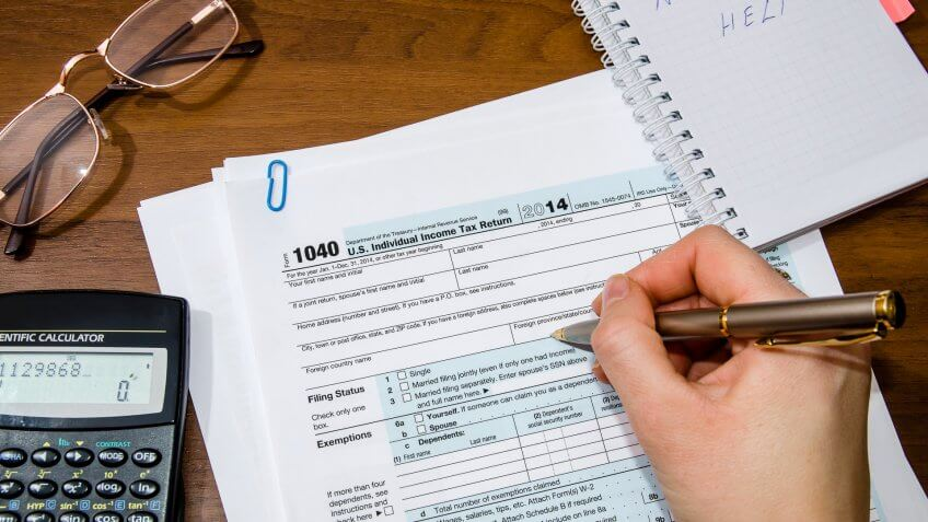 Woman hand filling income tax forms 1040Woman hand filling income tax forms 1040.