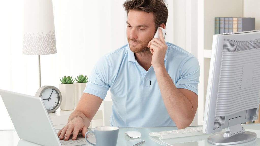 man on phone and laptop in home office