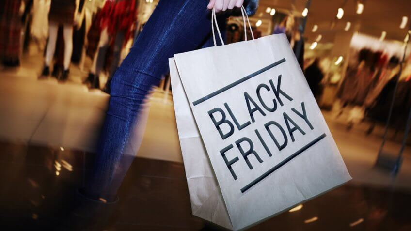 Modern shopper with Black Friday paperbag going in the mall.