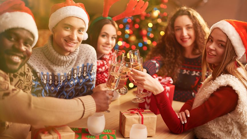 friends dressed in christmas apparel making a toast with champagne