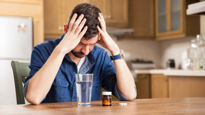 man in pain with aspirin and glass of water