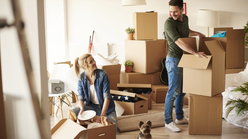 couple with unpacking moving boxes