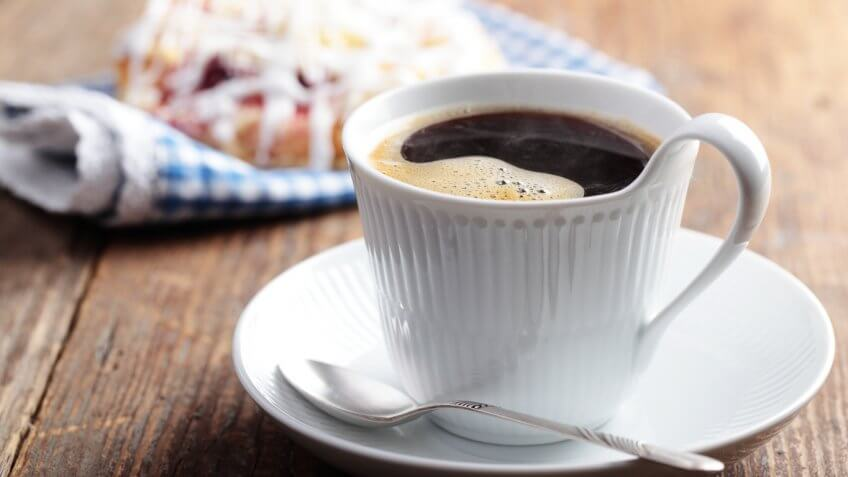 steaming black coffee in front of breakfast pastry
