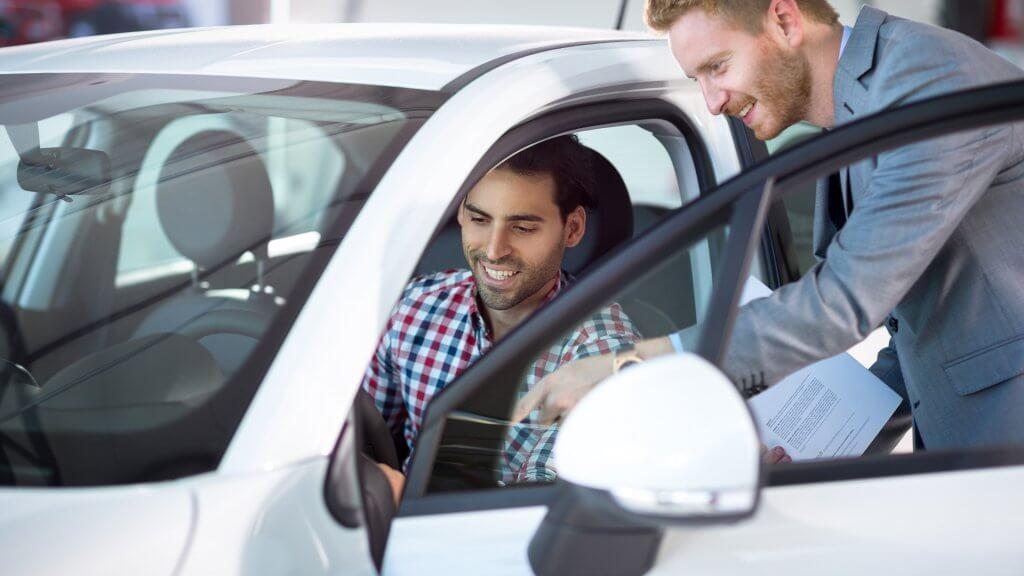 car salesman letting male customer sit in new car