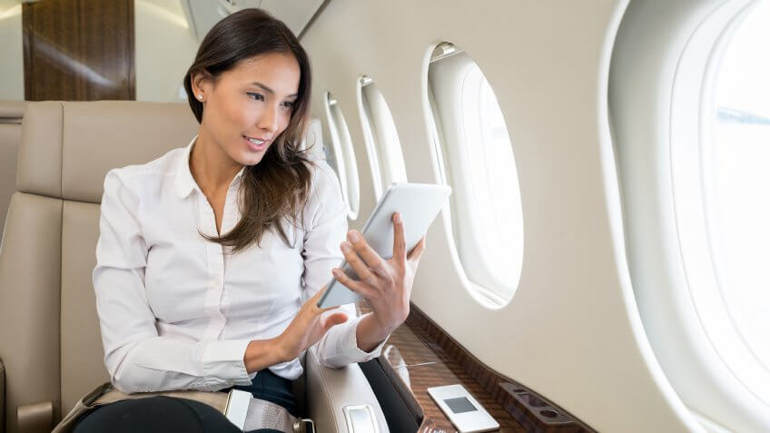 Business woman traveling and enjoying onboard entertainment on her tablet computer.