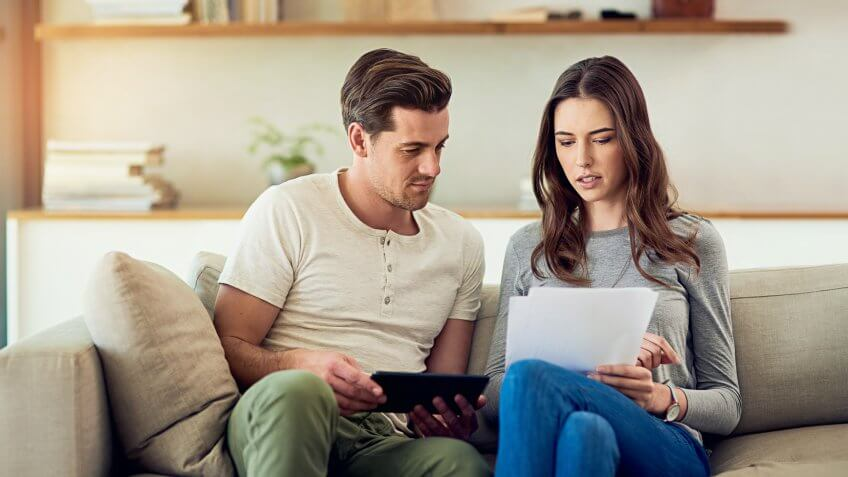Shot of a young couple going through their paperwork together at home.