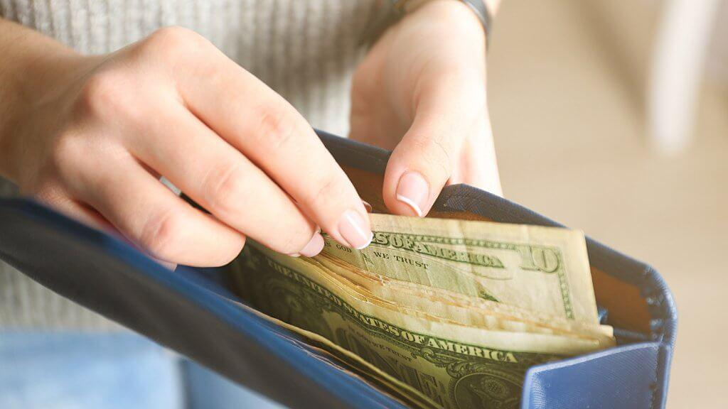 woman removing cash from purse