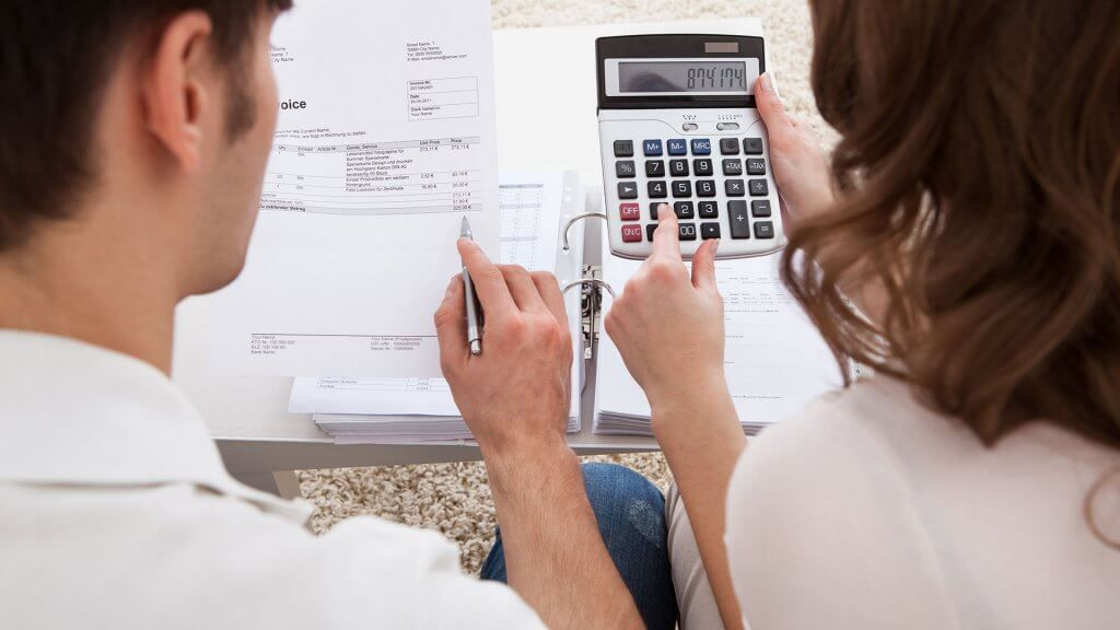 man and woman using calculator to determine finances