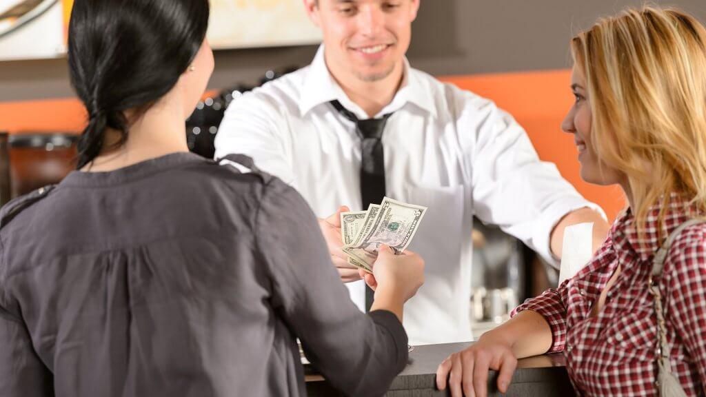 woman handing cash to barista