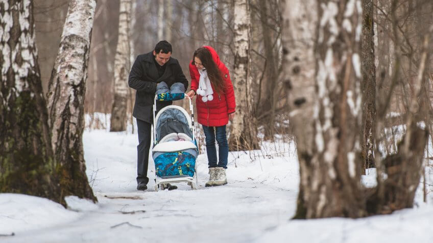 mother and father pushing baby in stroller through the woods