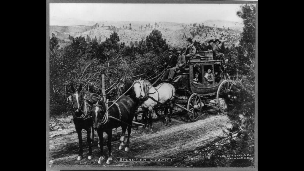 Photograph shows Spearfish stagecoach on dirt road with driver and passengers circa 1900 to 1910