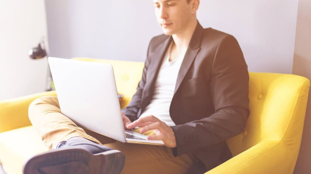 well-dressed man sitting on couch using laptop