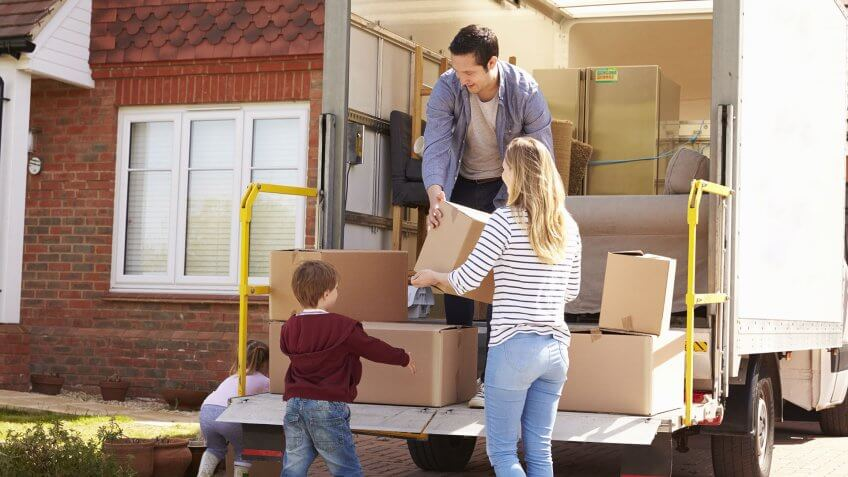 family lifting moving boxes into truck