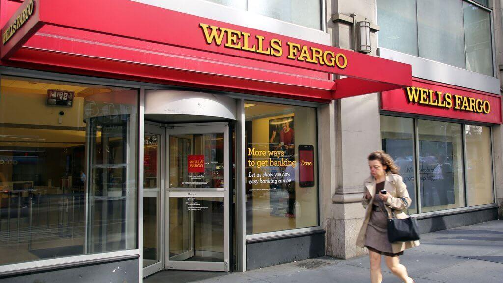 woman walking past a wells fargo bank