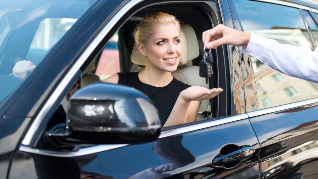 woman in car receiving keys from salesperson