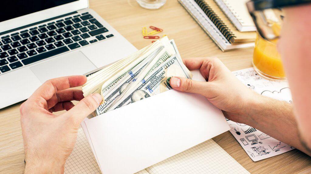 man holding envelope filled with 100 dollar bills