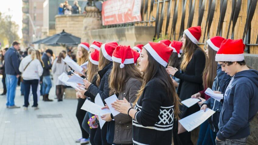 teen christmas choir singing on a busy sidewalk
