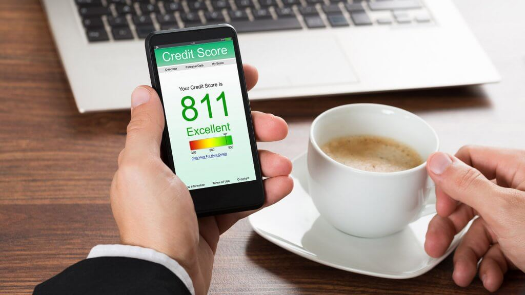 person drinking coffee has an excellent credit score on phone