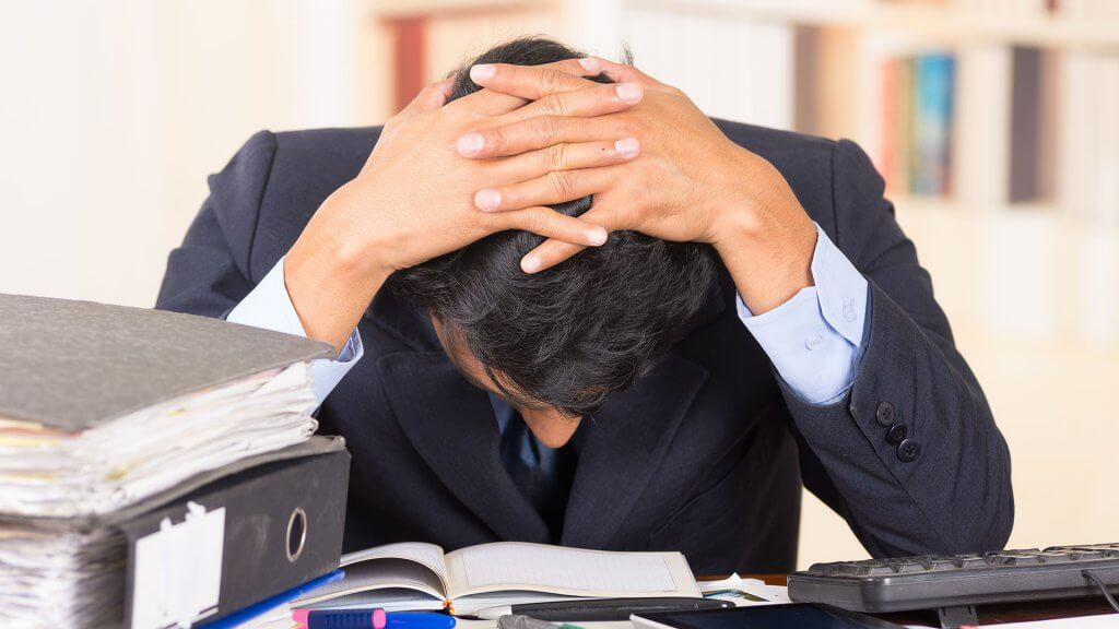 overwhelmed businessman with his head down on his desk